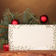 Blank postcard, Christmas balls and fir-tree on wooden table on brown backg — Stock Photo