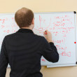 Man writing math formulas on a white-board — Stock Photo
