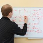 Man writing math formulas on a white-board — Stock Photo