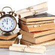 Pile of old books with clock and scroll isolated on white — Stockfoto