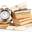 Pile of old books with clock and scroll isolated on white — Stock Photo