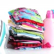 Pile of colorful clothes and electric iron with detergent isolated on white — Stok fotoğraf