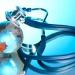 Globe and stethoscope on blue - Stock Photo