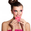 Young girl like a doll in pink dresses with heart-shaped candy isolated on — Stock Photo