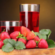 Fresh strawberry and juice glasses on wooden table on brown background - Stock Photo