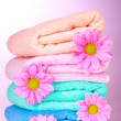 Towels and beautiful flowers on pink background - Stock Photo