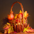 Royalty-Free Stock Photo: Beautiful autumn harvest in basket and leaves on brown background