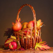 Beautiful autumn harvest in basket and leaves on brown background — Stock Photo