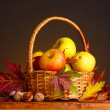 Beautiful autumn harvest in basket and leaves on brown background - Stock Photo