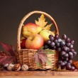 Beautiful autumn harvest in basket and leaves on brown background — Stock Photo #8118746