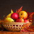 Beautiful autumn harvest in basket and leaves on brown background — Stock Photo #8118763