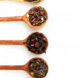 Different kinds of green and black dry tea in woooden spoon isolated on whi — Stock Photo #8118977