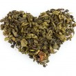Green dry tea heart shape isolated on white — Stock Photo