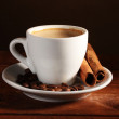 Cup with coffee, cinnamon and coffee beans on wooden table on brown backgr — Stock Photo