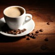 Cup with coffee and coffee beans on wooden table — Stock Photo