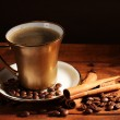 Golden cup with coffee, cinnamon and coffee beans on wooden table on brown — Stock Photo