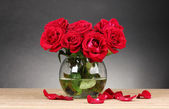 Beautiful red roses in vase on wooden table on gray background — Stock Photo