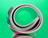 Rolled up magazines on green background — Stockfoto