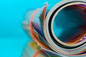Rolled up magazines on blue background — Stock Photo