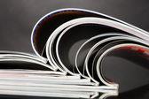 Open magazines on gray background — Stock Photo