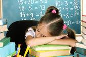 Little schoolgirl sleep in classroom near blackboard — Stock Photo