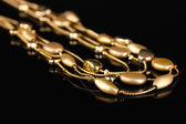 Beautiful gold necklace on black background — Stock Photo