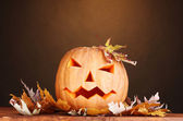 Halloween Pumpkin and autumn leaves on wooden table on brown background — Stock Photo