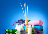 Bottle of air freshener, lavander, towels and candles on blue background — Stock Photo