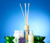 Bottle of air freshener, lavander and candles on blue background — Stock Photo