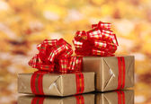 Beautiful golden gifts with red ribbon on yellow background — Stock Photo