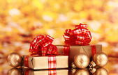 Beautiful golden gifts with red ribbon and Christmas balls on yellow backgr — Stock Photo