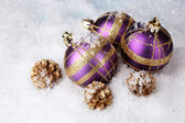 Beautiful blue and purple Christmas balls and cones on snow — Stock Photo