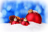 Beautiful red Christmas balls in snow on blue background — ストック写真