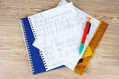 Math on copybook page on a wooden table — Stok fotoğraf