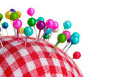 Colored pinheads in pin-cushion isolated on white — Stock Photo