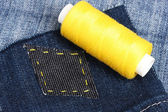 Rhomb-shaped patch on jeans with threads closeup — Stock Photo