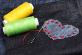 Heart-shaped patch on jeans with threads and needle closeup — Stock Photo