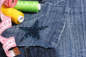 Star-shaped patch on jeans with threads and buttons closeup — Stock Photo