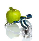Medical stethoscope and green apple isolated on white — Stock Photo