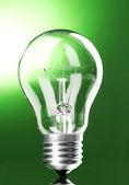 Light bulb on green background — Stock Photo