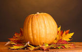 Dojrzałe dynia i liści jesienią na drewnianym stole na brązowym tle — Zdjęcie stockowe