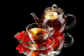 Glass teapot and cup with black viburnum tea isolated on black — Stock Photo