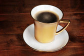 Golden cup of coffee on wooden table — Stock Photo