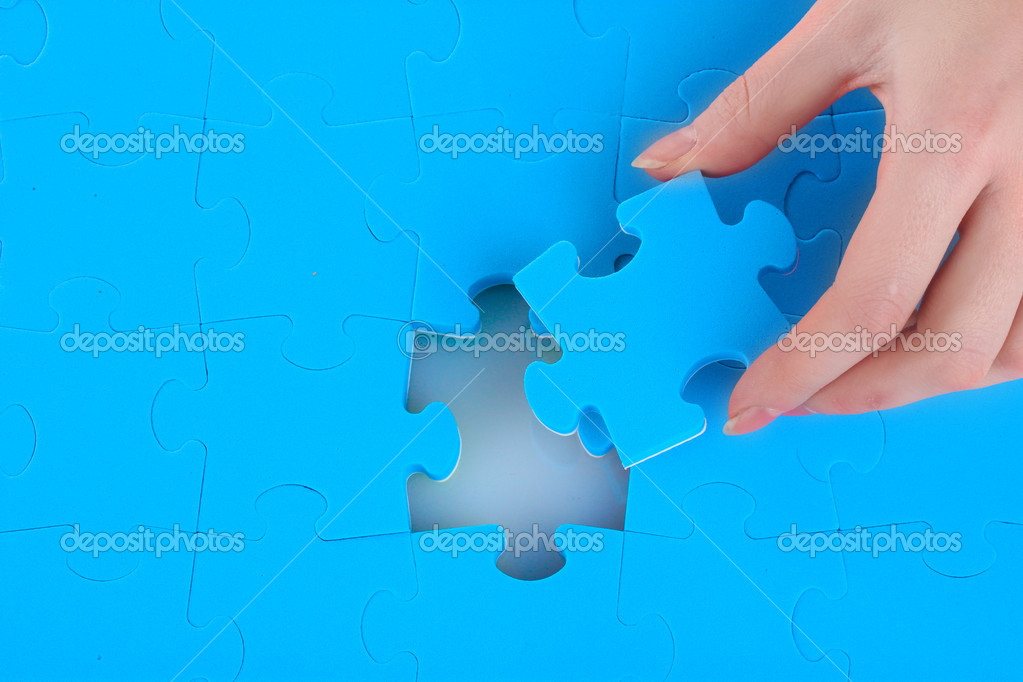 Hand collecting a part of a puzzle — Stock Photo #8114970