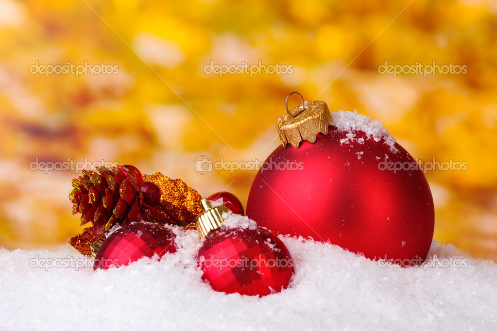 Beautiful red Christmas balls and branch in snow on yellow background — Stock Photo #8115366