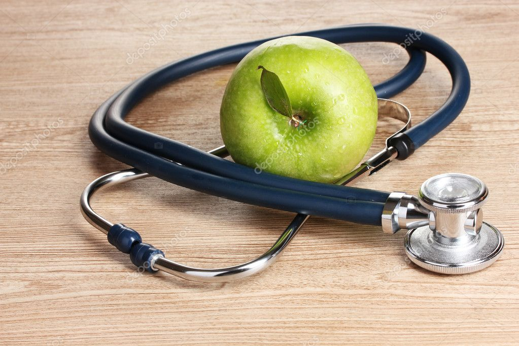 Medical stethoscope and green apple on wooden background — Stock Photo #8116918