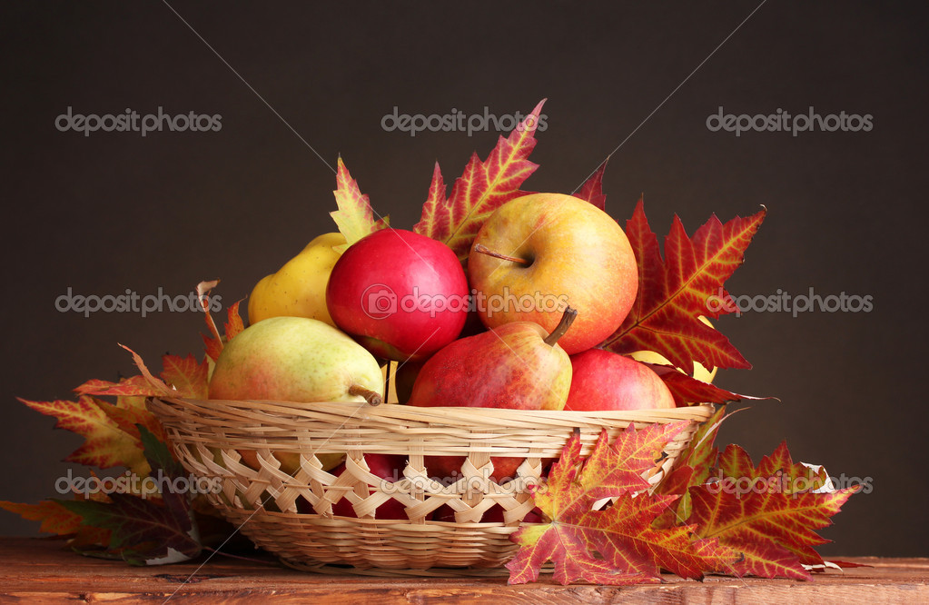 Beautiful autumn harvest in basket and leaves on brown background — Stock Photo #8118760