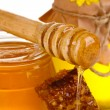 Two jars of honey, honeycombs and wooden drizzler closeup — Stock Photo