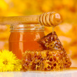 Jar of honey, honeycombs and wooden drizzler on yellow background — Stock Photo