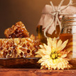Two jars of honey,honeycombs and wooden drizzler on table on yellow backgro — Stock Photo #8120368